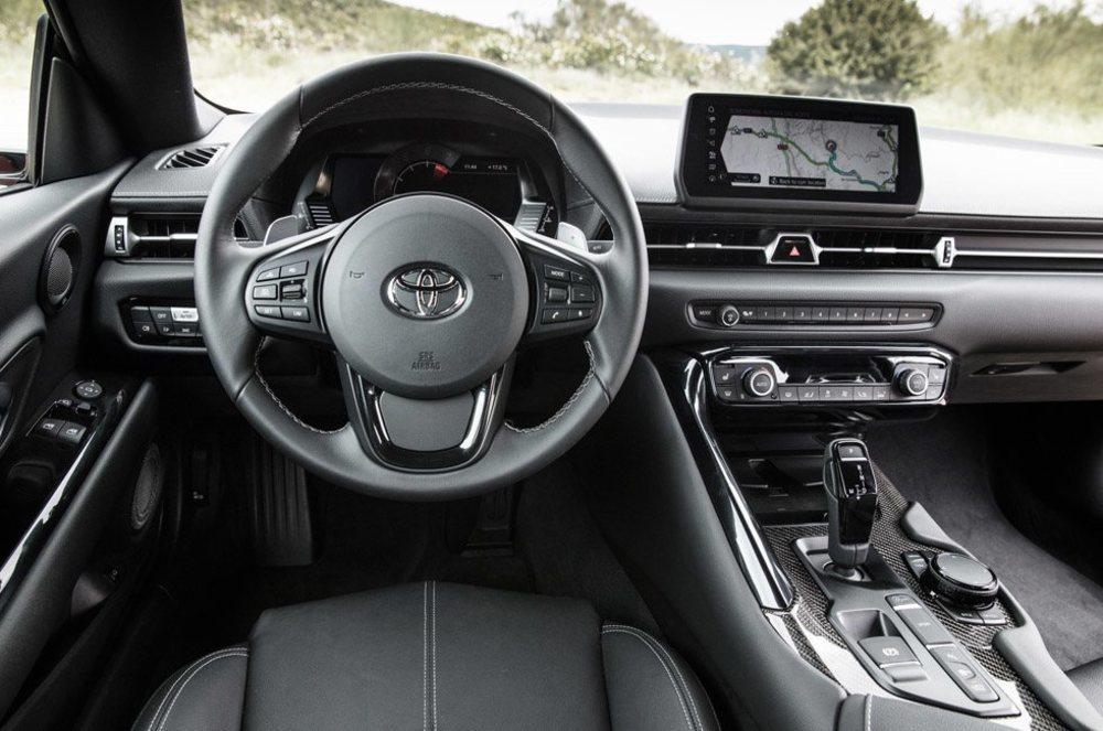 El interior del Toyota GR Supra tiene de la firma nipona el emblema y para de contar, pues el resto recuerda a BMW, su socio en el desarrollo junto al Z4. El cuadro digital, la pantalla central o las molduras de fibra de carbono son de serie.