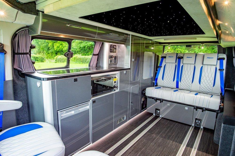 Wellhouse Leisure personaliza el interior de este Transit Custom Nugget con cuero y alcántara. También hay cinturones específicos y este módulo con cocina, nevera u horno nos hará sentirnos como en casa.
