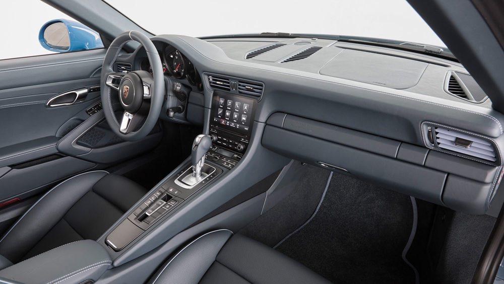 El habitáculo se tapiza en su totalidad en cuero de color grafito-azul, siempre en contraste con los pespuntes en color Provenza Azul. Hay detalles creados por Porsche Exclusive, como los umbrales de las puertas, que nos recuerdan que es una criatura única.