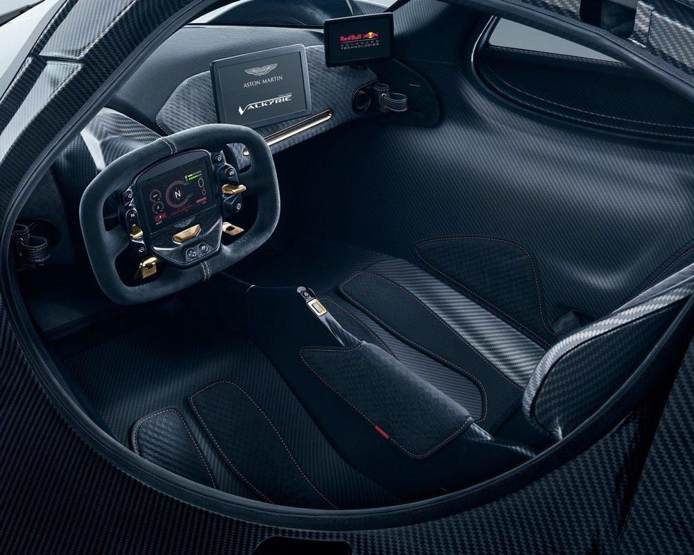 El interior es verdaderamente minimalista y sus dos asientos de carbono están anclados al chasis monocasco. Lo que se regularán serán sus pedales y su volante, que además se puede extraer para facilitar el acceso. Tras él hay una pantalla OLED para mantener informado al 'piloto'.
